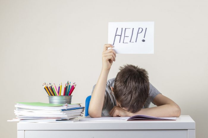 Sad tired frustrated boy sitting at the table with many books and holding help sign. Learning difficulties, education concept.
