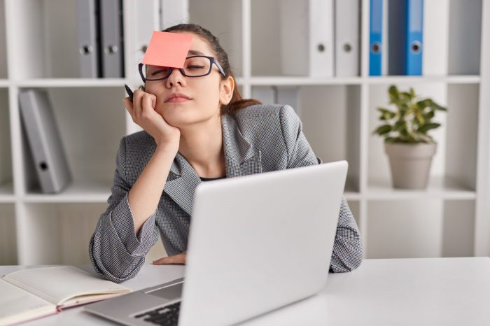 Tired young trainee with blank sticky note on forehead supporting head and sleeping during working day in office
